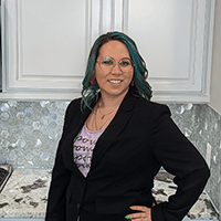 Heather smiles in front of white cabinets wearing a black blazer.