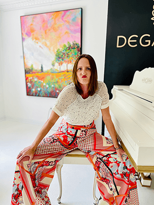 Erika Ervin straddles a piano bench while wearing bright clothes and a wrinkled, frustrated face.